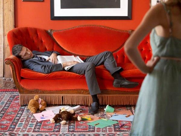 В комнате мужчина спит на красном диване, справа находится недовольная женщина, так как на полу разбросаны вещи
